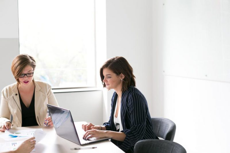 Two business women in white, sunlit room work at a boardroom table