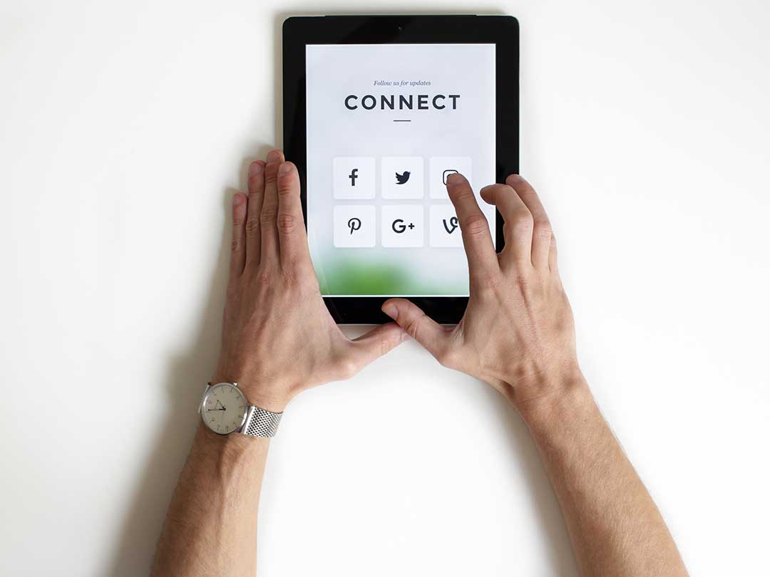 person holding tablet with social media icons